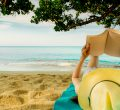 Woman Lie Down On Green Towel That Put On Sand Beach Under The T